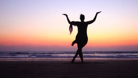 Woman in Pose dancing Shiva in Sunset pink Sky near sea  in India. Dance is  useful !   Symbol of India royalty free stock image