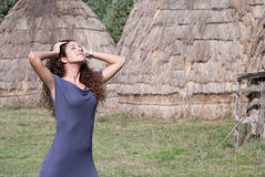 Woman pose front of straw houses. Woman wear dress and thick stockings pose with hands on head and closed eyes, enjoying the moment front of straw houses Stock Images
