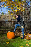 Woman pose with large pumpkin in autumnal park Stock Photo