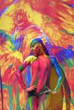 Woman poses for fotos at colorful background. Stock Photography