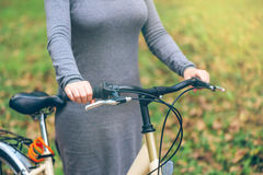Woman poses with her bicycle in park during autumn Royalty Free Stock Image