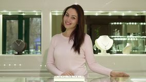 Woman poses at the jewelry boutigue. Attractive caucasian woman posing at the jewerly boutique. Beautiful young lady holding her hands on showcase with jewels Stock Photos