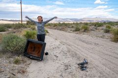 Woman poses with an old busted broken CRT television in the middle of the desert, near the Salton Sea of California.  stock image