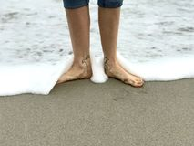 WOMAN POSES IN THE SURF WITH ANKLE TATTOOS OF A MAP OF THE 7 CONTINENTS. A shot of a female showing her love for travel and exploration on a Florida beach royalty free stock image