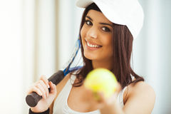 Woman poses with a tennis racket while holding tennis ball Stock Images