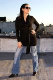Woman posing. A woman posing as a fashion model in a black long shirt and jeans. She's wearing sunglasses and is looking into the sun stock photography