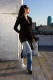 Woman posing. A woman posing as a fashion model in a black long shirt and jeans. She's wearing sunglasses and is looking into the sun. There's a skyscraper in royalty free stock photography