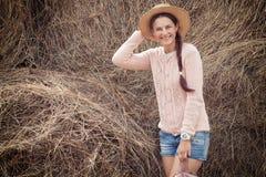 Woman posing against haystacks stock images