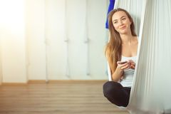 Woman posing in anti-gravity aerial yoga hammock. relax with phone Royalty Free Stock Image