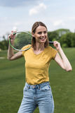 Woman posing with badminton racquet and shuttlecock while looking away. Happy woman posing with badminton racquet and shuttlecock while looking away Royalty Free Stock Photos