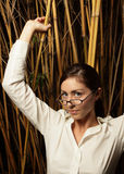 Woman posing by bamboo plants Stock Images