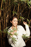 Woman posing by bamboo plants Royalty Free Stock Photography