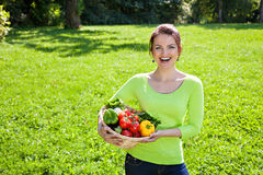 Woman posing with basket full of vegetables Royalty Free Stock Photo