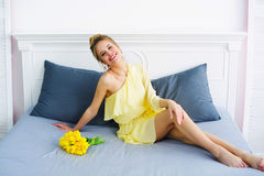 Woman posing on bed with flowers Royalty Free Stock Photography