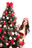 Woman posing behind a Christmas tree. Vertical shot of a young woman in Santa costume posing behind a Christmas tree isolated on white background Royalty Free Stock Photo