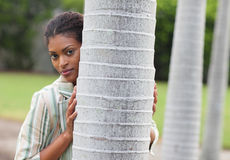 Woman posing behind a tree Stock Image