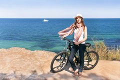 Woman is posing with bicycle on a background of the sea. stock image