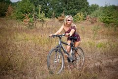 Woman posing on bicycle Royalty Free Stock Photography