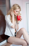 Woman posing with a big red cup of tea in her hands Royalty Free Stock Images