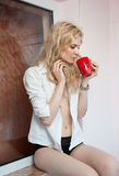 Woman posing with a big red cup of tea in her hands Royalty Free Stock Photography