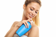 Woman posing with body lotion over white background. Picture showing woman with body lotion over white background Stock Images