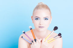 Woman posing with bunch of professional make-up brushed Royalty Free Stock Images