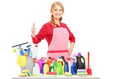 Woman posing with cleaning supplies and giving a thumb up. Isolated on white background royalty free stock photo