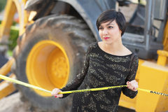 Woman posing by construction equipment Stock Photography