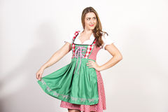 Woman posing in dirndl dress against a white wall. Royalty Free Stock Image