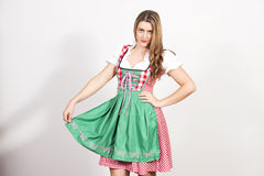 Woman posing in dirndl dress against a white wall. Stock Photography