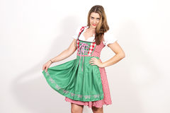 Woman posing in dirndl dress against a white wall. Royalty Free Stock Photos