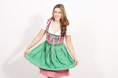 Woman posing in dirndl dress against a white wall. Royalty Free Stock Images