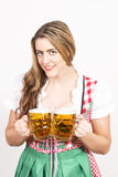 Woman posing in dirndl dress against a white wall. Stock Images