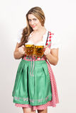 Woman posing in dirndl dress against a white wall. Stock Image