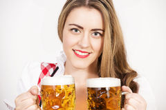 Woman posing in dirndl dress against a white wall. Stock Photos