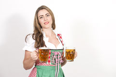Woman posing in dirndl dress against a white wall. Royalty Free Stock Photography