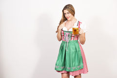Woman posing in dirndl dress against a white wall. Royalty Free Stock Photo