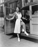 Woman posing at door of car Stock Images