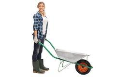 Woman posing with empty wheelbarrow Royalty Free Stock Photography