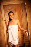 Woman posing at entrance of sauna. Attractive woman wearing towel posing at entrance of sauna, opening door, smiling Royalty Free Stock Images