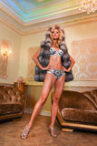 Woman posing in a fashionable lingerie and fur coat. Modern and luxury interior. Royalty Free Stock Photo