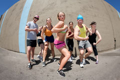 Woman posing with fellow athletes. Pretty female runner poses with fellow athletes Stock Photos