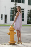 Woman posing by a fire hydrant Stock Photography