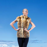 A woman posing in a fur jacket on a sky background Stock Photo
