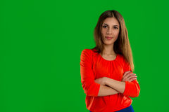 Woman posing on green background. Serious young brunette woman in studio on green background looking at the camera Royalty Free Stock Image