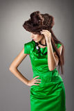 Woman posing in green dress and hair style hat Stock Images