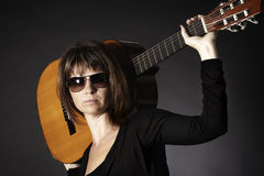 Woman posing with guitar on shoulders. Stock Photo