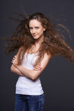 Woman posing with hair fluttering in the wind. Portrait of fashion model posing with hair fluttering in the wind royalty free stock photo