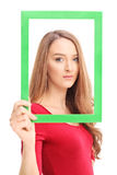 Woman posing and holding a picture frame Royalty Free Stock Images