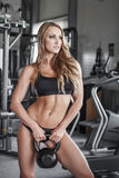 Woman posing with kettlebell in gym Stock Photography